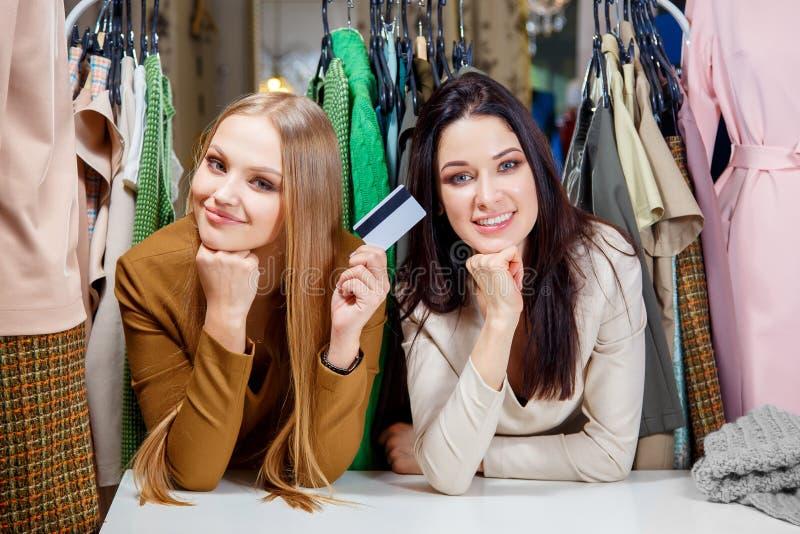 Twee jonge mooie meisjes maken het winkelen met een creditcard en het glimlachen in een kledingsopslag stock fotografie