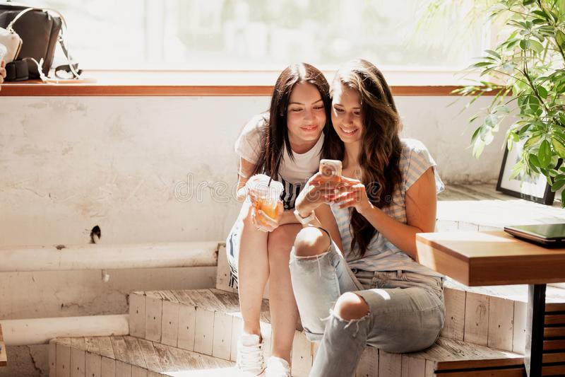 Twee jonge mooie meisjes met lang donker haar, die toevallige uitrusting dragen, zitten bij de treden en bekijken de telefoon in  stock fotografie