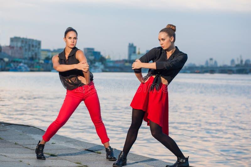 Twee jonge mooie tweelingzusters zijn het dansen waacking dans op de stadsachtergrond dichtbij rivier royalty-vrije stock afbeelding