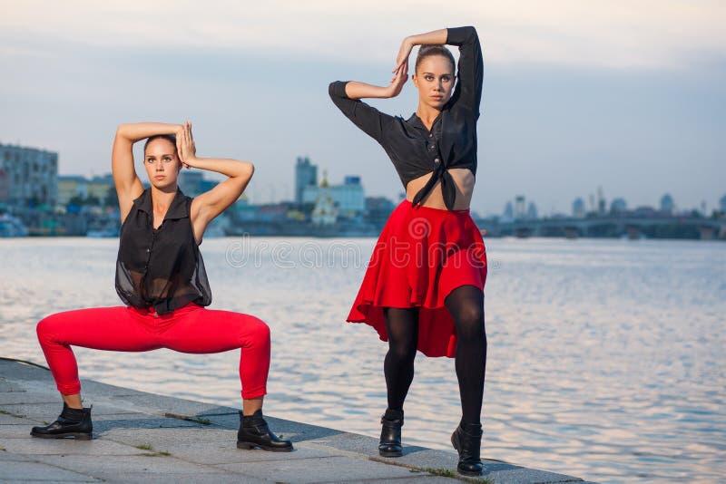 Twee jonge mooie tweelingzusters zijn het dansen waacking dans op de stadsachtergrond dichtbij rivier royalty-vrije stock foto's