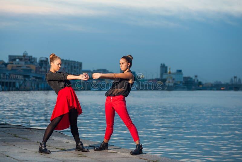 Twee jonge mooie tweelingzusters zijn het dansen waacking dans op de stadsachtergrond dichtbij rivier stock afbeeldingen