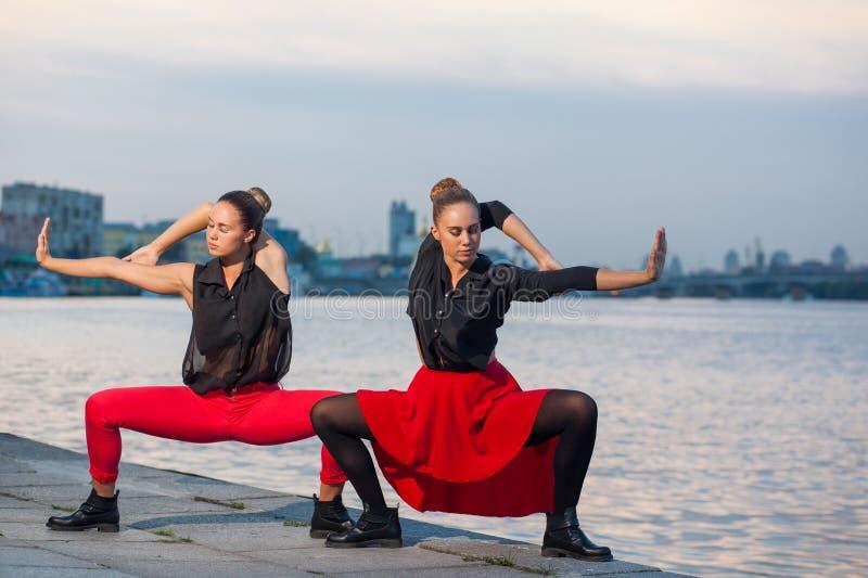 Twee jonge mooie tweelingzusters zijn het dansen waacking dans op de stadsachtergrond dichtbij rivier stock foto's