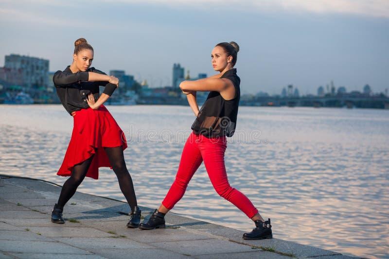 Twee jonge mooie tweelingzusters zijn het dansen waacking dans op de stadsachtergrond dichtbij rivier royalty-vrije stock afbeeldingen