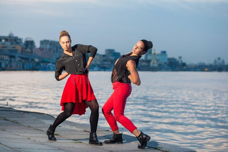Twee jonge mooie tweelingzusters zijn het dansen waacking dans op de stadsachtergrond dichtbij rivier royalty-vrije stock fotografie