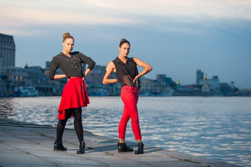 Twee jonge mooie tweelingzusters zijn het dansen waacking dans op de stadsachtergrond dichtbij rivier stock afbeelding
