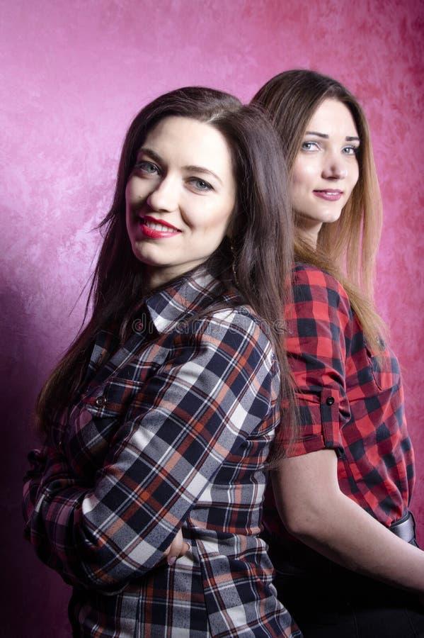 Twee jonge mooie vrouwen in de tribune van plaidoverhemden met hun ruggen aan elkaar royalty-vrije stock foto