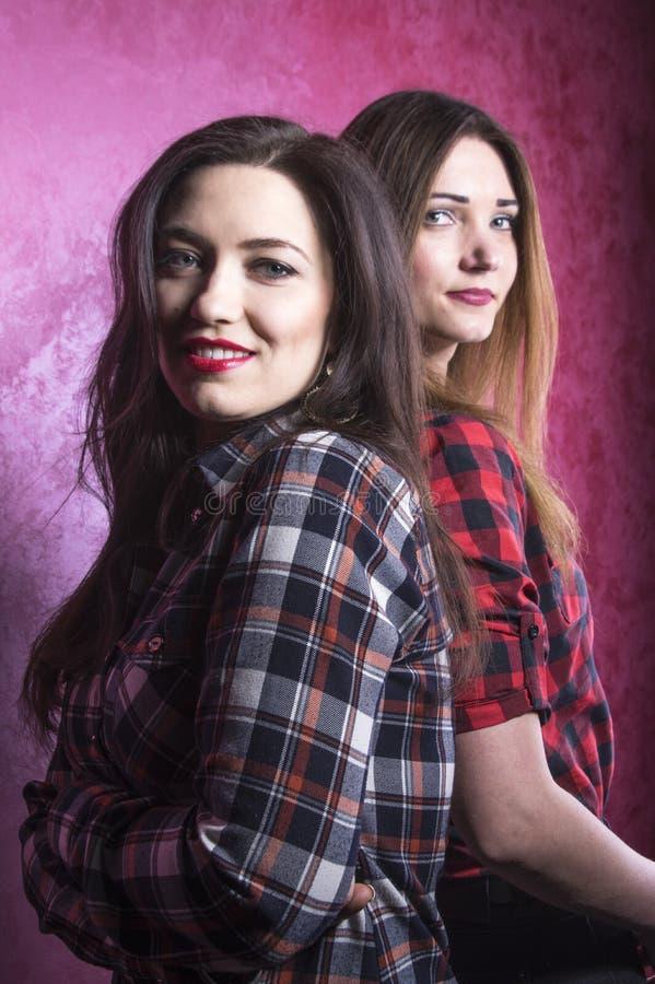 Twee jonge mooie vrouwen in de tribune van plaidoverhemden met hun ruggen aan elkaar royalty-vrije stock foto's