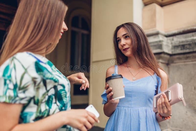 Twee jonge mooie vrouwen die het drinken koffie spreken Meisjes die pret in stad hebben De beste vrienden babbelen in openlucht royalty-vrije stock foto's