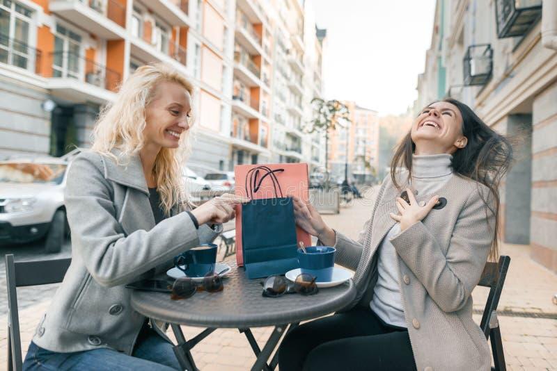 Twee jonge mooie vrouwen in een openluchtkoffie met het winkelen zakken en kop van koffie Het genieten van van vrouwen die aankop royalty-vrije stock foto's