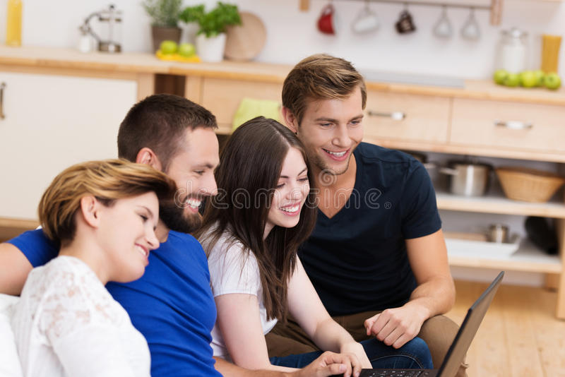 Twee jonge paren die laptop delen stock afbeelding