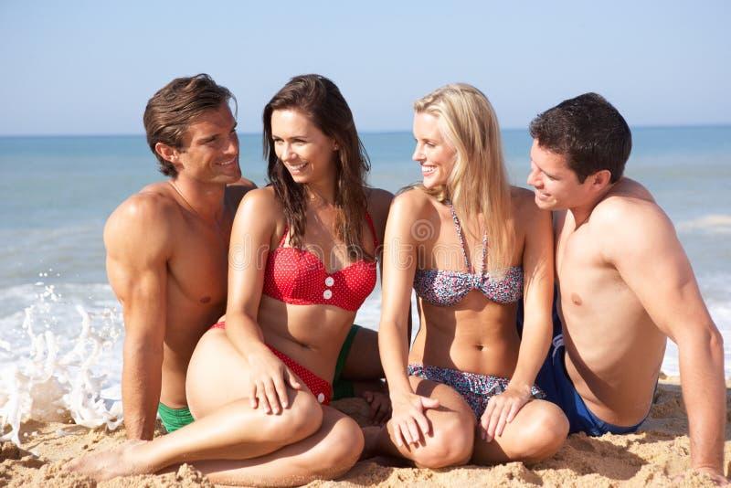 Twee jonge paren op strandvakantie stock fotografie