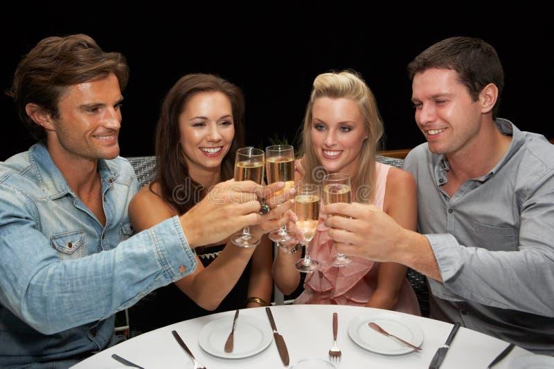 Twee jonge paren in restaurant royalty-vrije stock afbeeldingen
