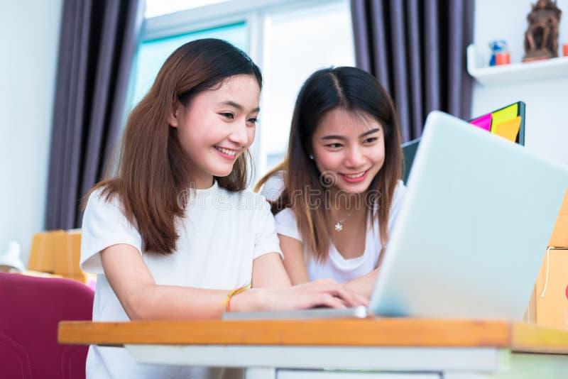 Twee jonge priv? onderneemsters van het freelancer Aziatische meisje thuis werkend bureau met laptop of computer met notitieboekj royalty-vrije stock afbeelding