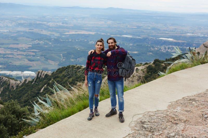 Twee jonge reizigers die op iets in de afstand wijzen aan zijn meisje royalty-vrije stock afbeeldingen