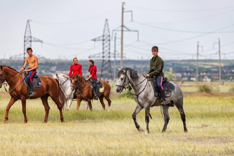 Twee jonge ruiters gaan rond hun paarden op het gebied vóór de rassen royalty-vrije stock afbeelding