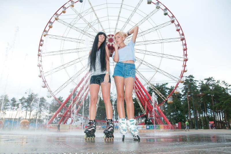 Twee jonge sensuele vrouwen die in park schaatsen royalty-vrije stock afbeelding