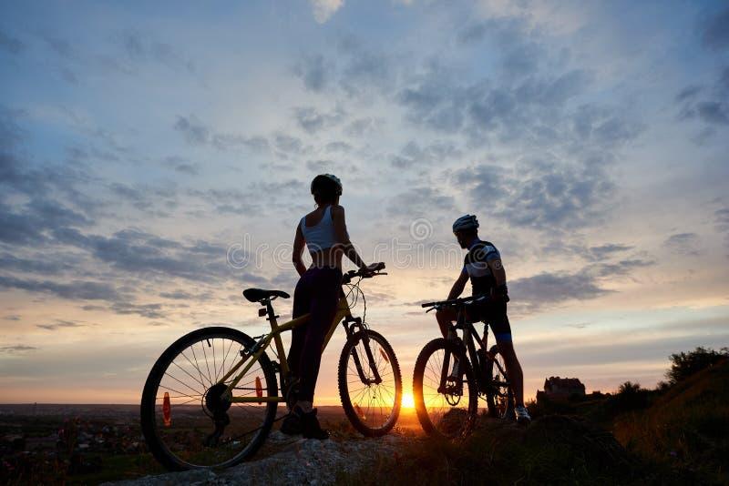 Twee jonge sportenmensen op bergfietsen bevinden zich op rots boven heuvel zoekend zonsondergang stock foto's