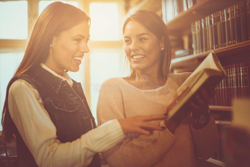 Twee jonge studentenmeisjes die boek in bibliotheek lezen royalty-vrije stock afbeeldingen