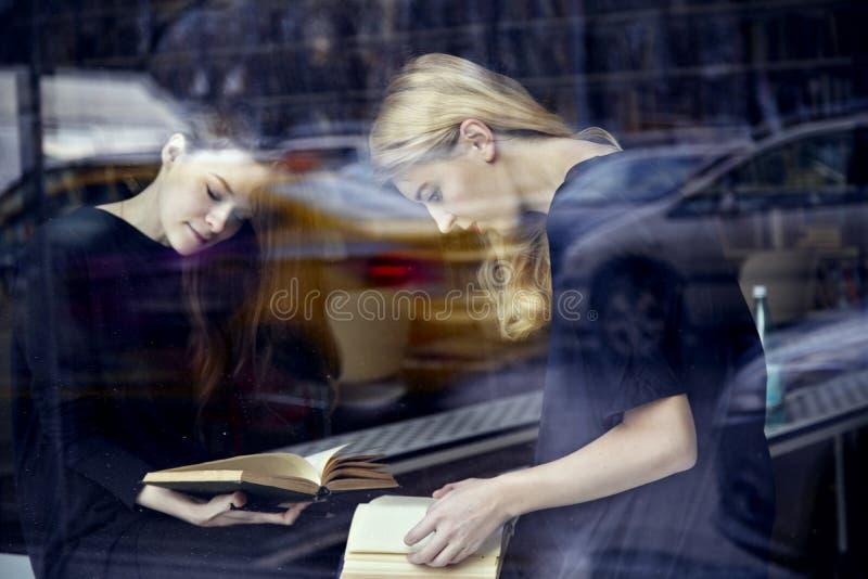 Twee jonge studentenvrouwen in de boeken van een bibliotheeklezing Zittingsnea stock foto