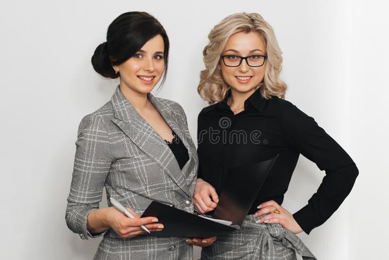 Twee jonge succesvolle onderneemstermeisjes met aantrekkelijke glimlachen royalty-vrije stock afbeeldingen