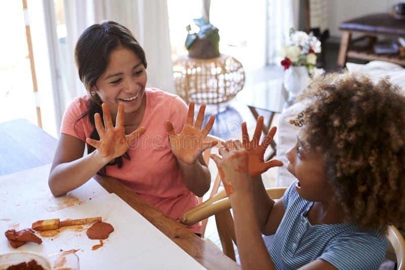 Twee jonge tiener en pre-tienermeisjes die bij een lijst zitten die thuis modelleringsklei gebruiken, die elkaar hun vuile handen stock foto