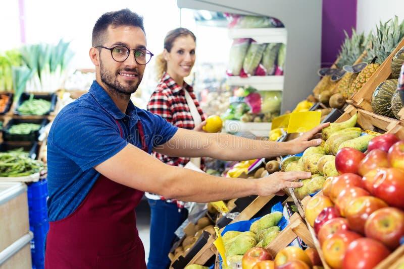 Twee jonge verkopers die camera bekijken en voor werkdag in fruitshop voorbereidingen treffen stock afbeeldingen