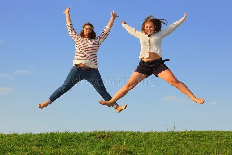 Twee jonge vette meisjes springen bij gras stock foto's