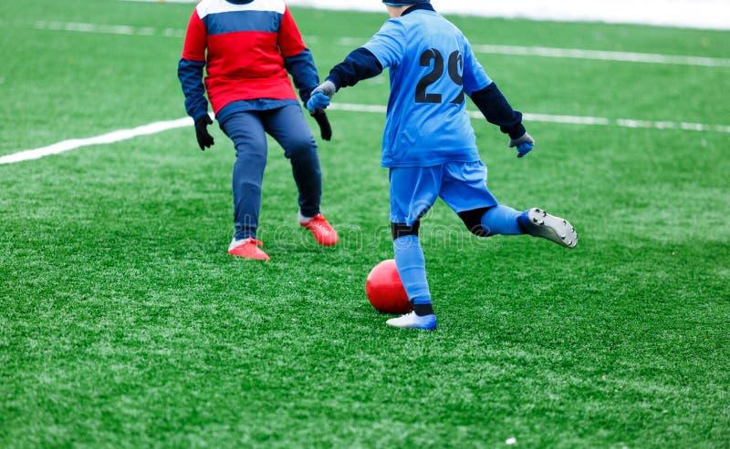 Twee jonge Voetballers in het rode en blauwe sportkleding lopen, dribble en het concurreren voor bal Junior Football Match Compet stock fotografie