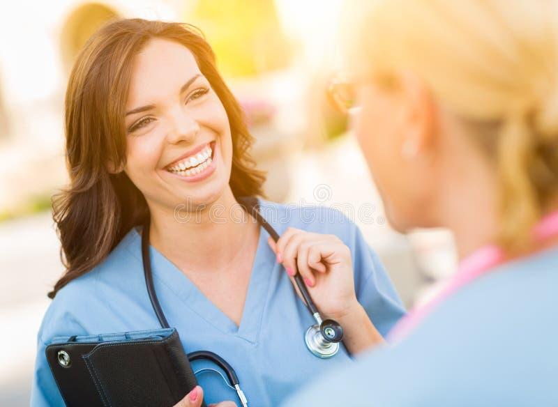 Twee Jonge Volwassen Professionele Vrouwelijke Artsen of Verpleegsters die Ou spreken stock foto's