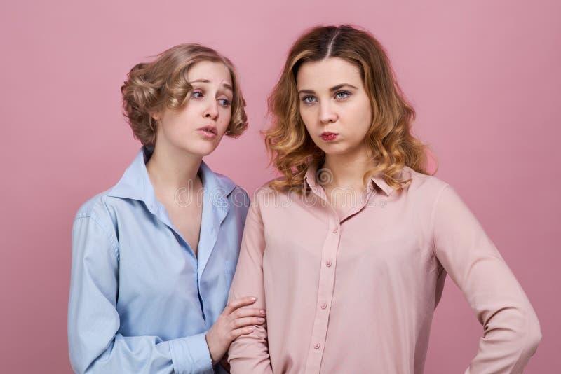Twee jonge vrienden verzoenen Het concept verontschuldiging en wrok het meisje in het blauwe overhemd vraagt om vergiffenis van v royalty-vrije stock afbeelding