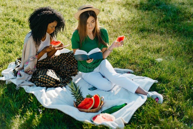 Twee jonge vrij Afrikaanse en Kaukasische meisjesvrienden die de watermeloen op een picknick eten Donkerbruine babbelt en royalty-vrije stock afbeeldingen