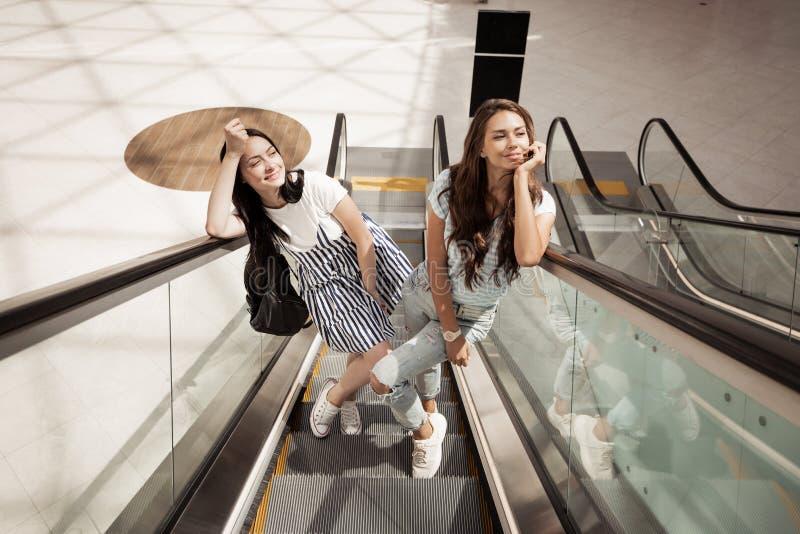Twee jonge vrij slanke meisjes, die toevallige stijl dragen, bevinden zich naast elkaar bij de roltrap royalty-vrije stock afbeeldingen