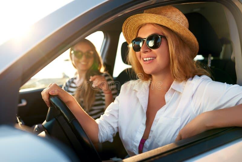 Twee jonge vrolijke glimlachende vrouwen in een auto op vakantie halen aan het overzeese strand over Meisje in glazen die een voe royalty-vrije stock afbeeldingen