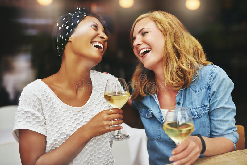 Twee jonge vrouwelijke en vrienden die vieren lachen stock foto