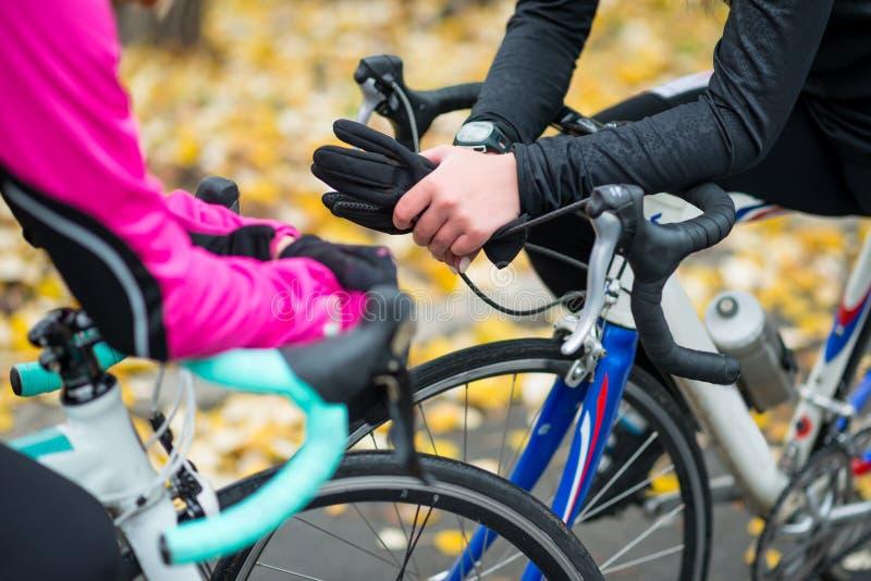 Twee Jonge Vrouwelijke Fietsers met Wegfietsen die in het Park in Koud Autumn Day rusten Gezonde Levensstijl royalty-vrije stock afbeeldingen