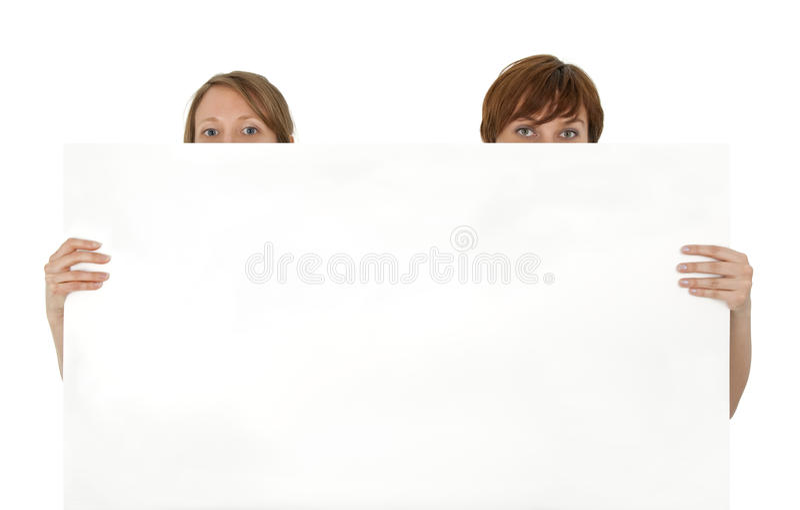 Twee jonge vrouwen achter een lege banneradvertentie royalty-vrije stock afbeeldingen