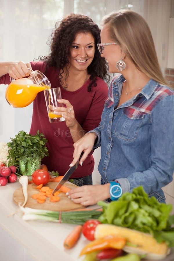 Twee jonge vrouwen in de keuken, het dieet en het gezonde het levensconcept stock afbeeldingen