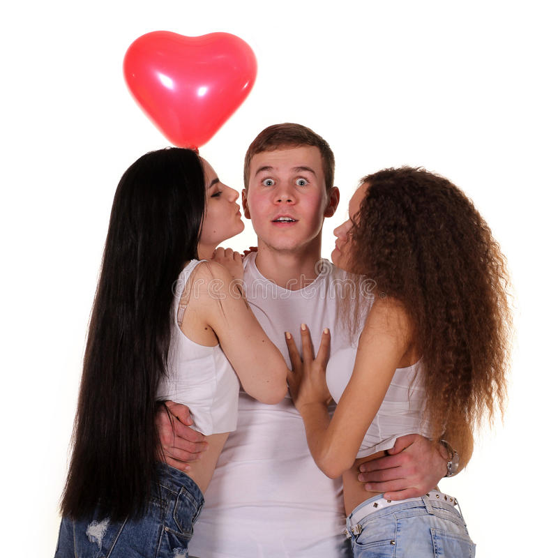 Twee jonge vrouwen die aan de man kussen stock foto