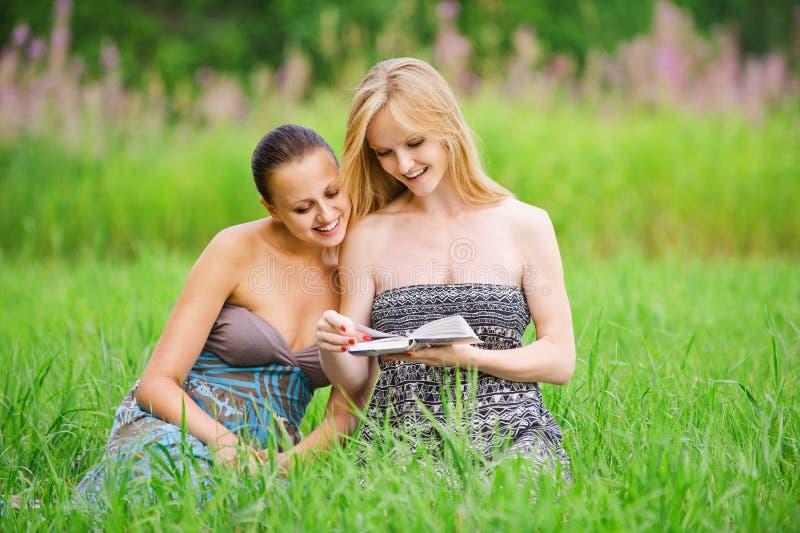 Twee jonge vrouwen die boek lezen royalty-vrije stock afbeelding