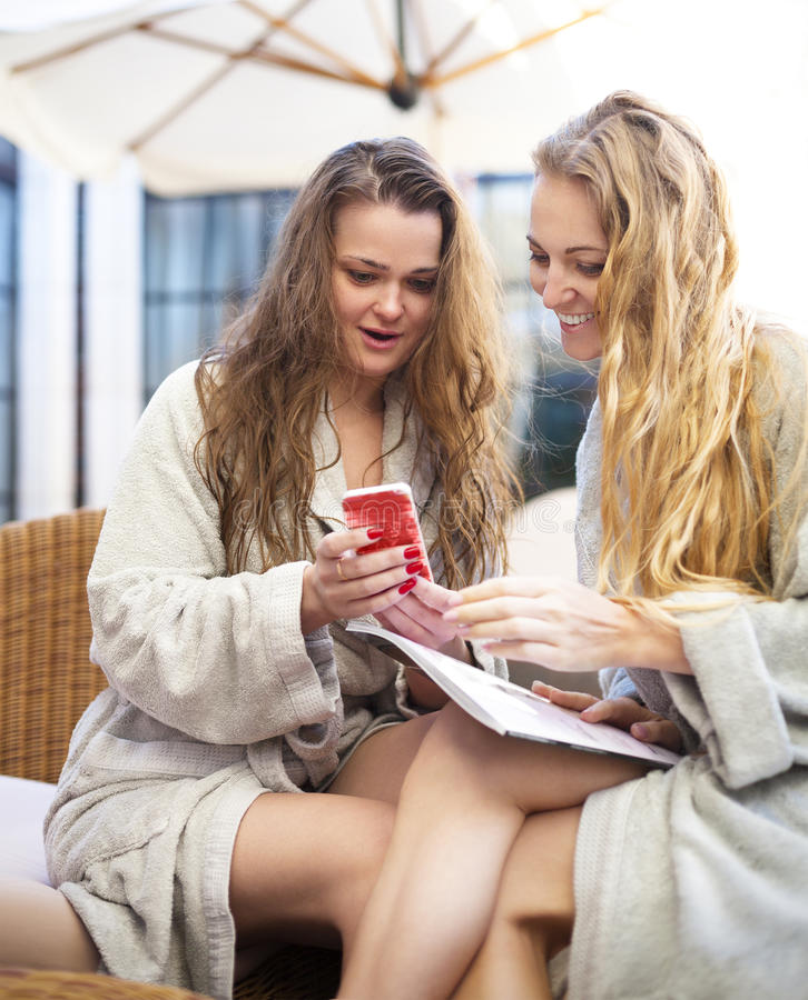 Twee jonge vrouwen die in de kuuroordtoevlucht ontspannen die toweling robe dragen stock foto