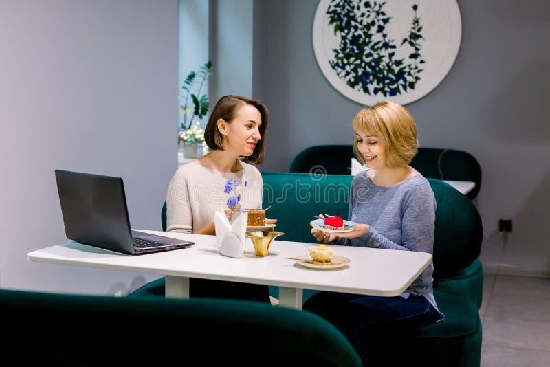 Twee jonge vrouwen die een dessert eten in café Gossiers met beste vriend Horizontale foto van een mooie vrouw die met haar praat stock fotografie