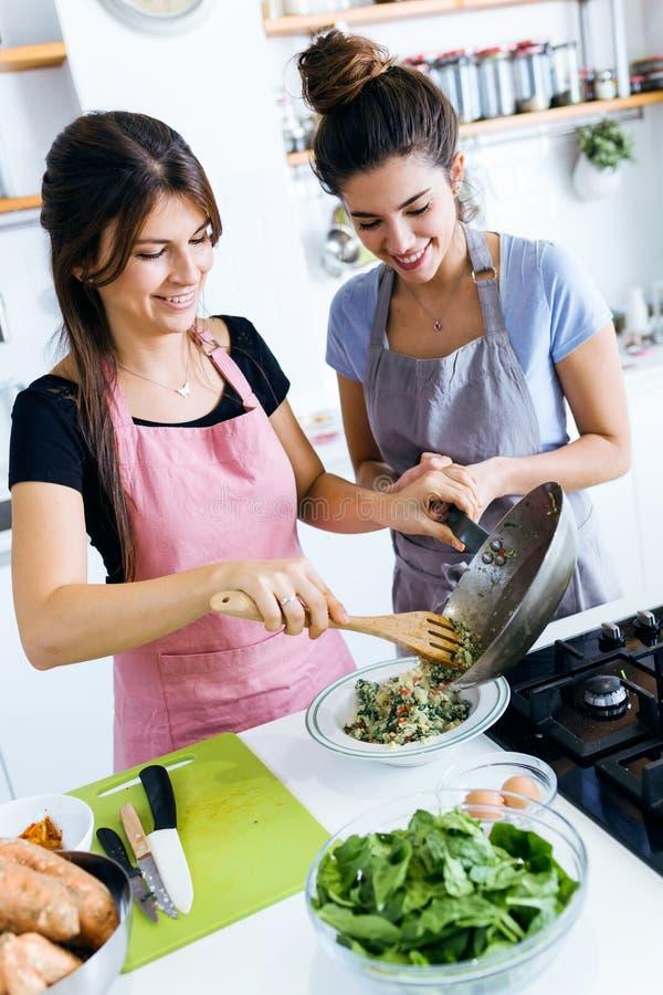 Twee jonge vrouwen die een plantaardig be*wegen-gebraden gerecht op de plaat dienen stock afbeeldingen