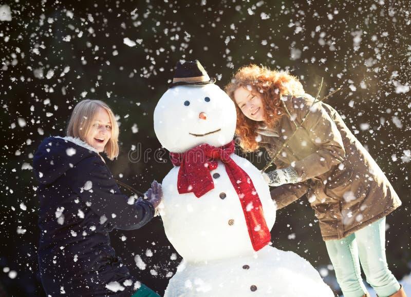 Twee jonge vrouwen die een sneeuwman bouwen stock foto