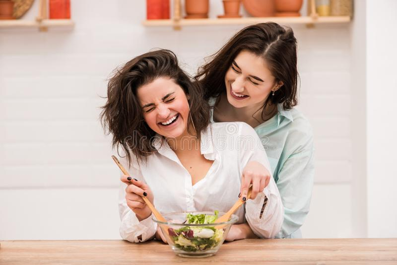 Twee jonge vrouwen die en bij keuken koken koesteren royalty-vrije stock foto