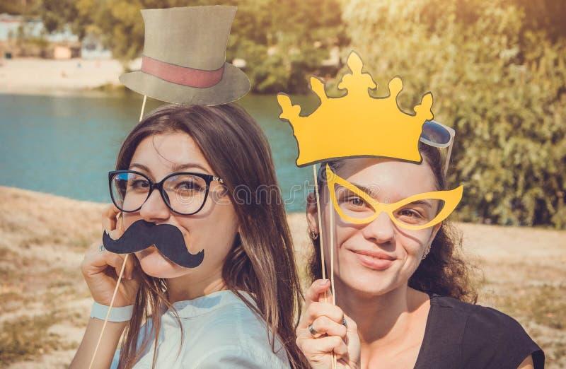 Twee jonge vrouwen die gebruikend de steunen van de fotocabine stellen royalty-vrije stock afbeeldingen
