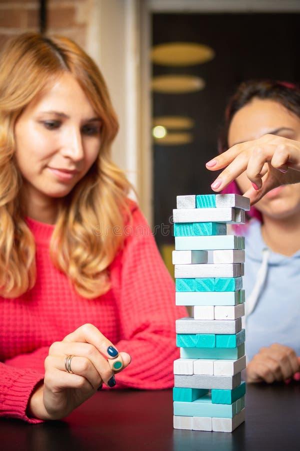 Twee jonge vrouwen die gekleurde jenga spelen stock afbeelding