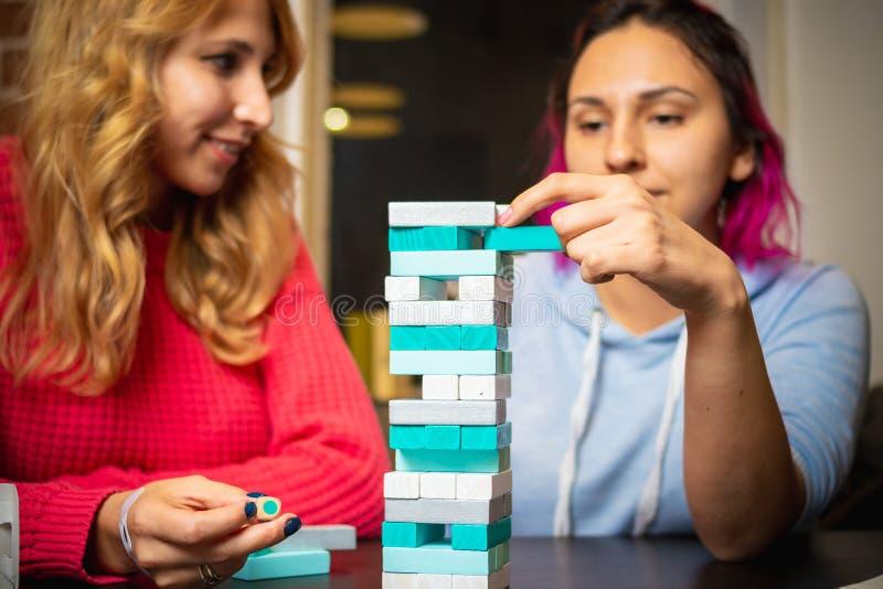 Twee jonge vrouwen die gekleurde jenga spelen royalty-vrije stock afbeeldingen