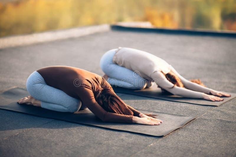 Twee jonge vrouwen die het kind ` s doen van yogaasana stellen op dakoutdoo royalty-vrije stock foto's