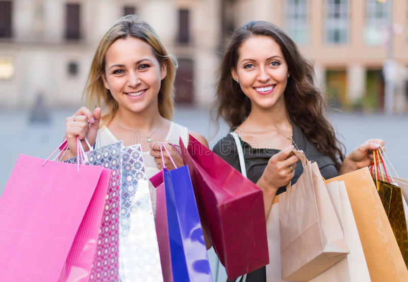 Twee jonge vrouwen die het winkelen zakken houden stock fotografie