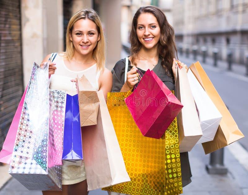Twee jonge vrouwen die het winkelen zakken houden royalty-vrije stock afbeelding